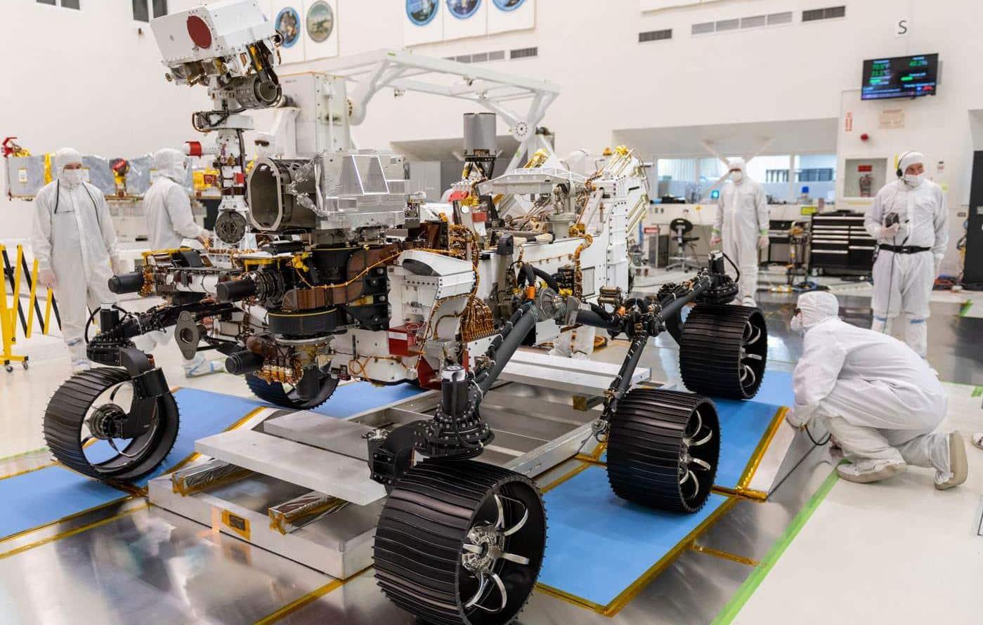 L'image montre le rover Perseverance en cours de préparation par des techniciens dans un laboratoire de la NASA