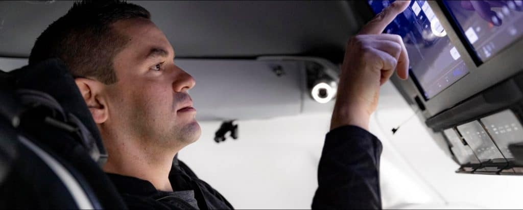 Le commandant de mission Inspiration4, Jared Isaacman, ajuste les commandes dans une cabine