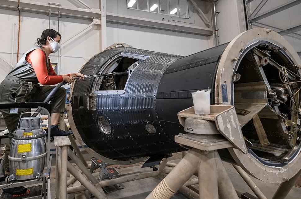 L'image montre un restaurateur du Smithsonian Museum chargé de restaurer la première combinaison de l'astronaute Alan Shepard, ainsi que la capsule où il a commandé le premier voyage américain dans l'espace