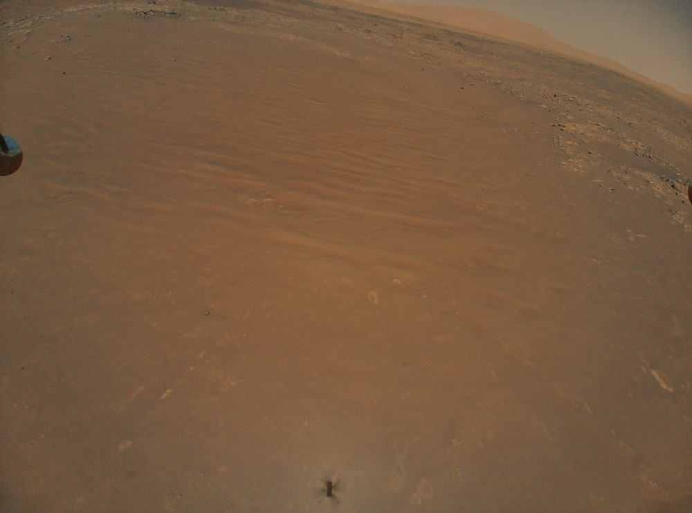 L'image montre une image aérienne de l'hélicoptère Ingenuity enregistrant le rover Perseverance sur Mars