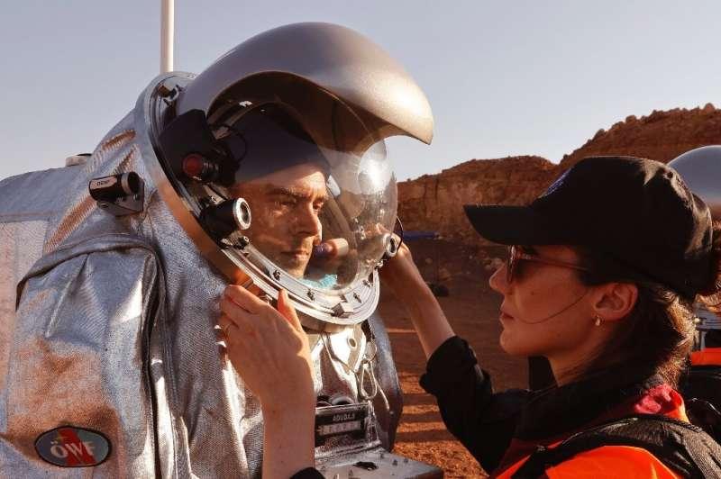 Des techniciens aident à adapter une combinaison d'astronaute dans un projet qui simule la vie sur Mars en Israël